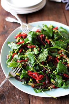 A vibrant pea and baby kale salad with sweet red peppers flavoured with mustard seeds, chilli, ginger, cloves and apple cider vinegar.