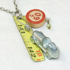 Monopoly car and bingo, measured. Upcycled necklace made with game pieces and tape measure.