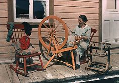 A woman spins yarn while seated on a porch. Quebec