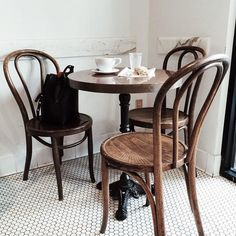 Small table with three chairs set at angles around table instead of chairs with your back facing to rest of room. Also note how one chair does sit a bit in front of the doorway but is still easily workable.