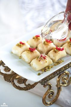A delectable Arabic dessert made from rolls of soft, sweet cheese dough that gets stuffed with clotted cream, and crowned with pistachios and rose petal jam. A drizzle of syrup flavored with orange blossom and rose water puts the final seal of perfection Arabic Dessert, Arabic Sweets, Arabic Food, Lebanese Desserts, Lebanese Recipes, Clotted Cream, Comida Armenia, Middle Eastern Desserts, Cheese Rolling