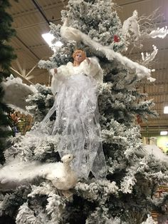 White Angel and peacock Christmas tree. Designed by Arcadia Floral and Home Décor