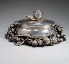 A SILVER LIDDED TUREEN, BY CARTIER Designed as an oval-shaped silver bowl, enhanced by silver onions, chestnuts, tomatoes and pomegranates, to the lid with a silver snail handle