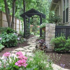 A once plain and severe side yard gets a makeover with window boxes, an arbor, stone pathway and walls to hide an unattractive air conditioning unit. | thisoldhouse.com