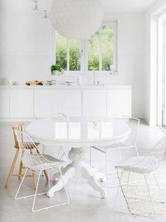 Mi comedor hay una mesa blanca y sillas blancas y de madera y hay arriba una lámpara de araña bola blanca