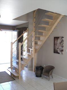 Escalier d'intérieur en bois d'hévéa, bois exotique clair et robuste très utilisé dans la fabrication de nos escaliers. Escalier 1/4 tournant à limon central en bois sans contre marche. Style épuré, escalier moderne et aérien qui laisse passer la lumière. Le garde-corps de l'escalier est en bois et câbles en inox.