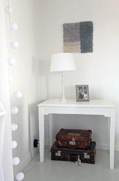 Valkoinen valosarja ja valkoinen pöytälamppu, valkoinen sivupöytä, harmaa pieni ryijy. White lights, white table lamp, white small and old side table.