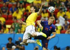Brazil's Maxwell and Dirk Kuyt of the Netherlands fight for the ball. REUTERS/Dominic Ebenbichler