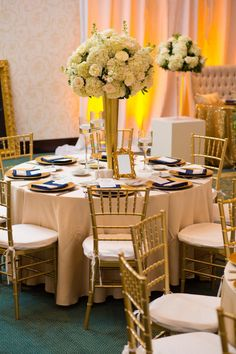 Gold Wedding Reception with Tall Ivory and White Centerpieces and Gold Chargers and Chiavari Chairs