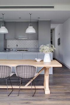 szara kuchnia z białą glazurowana cegiełka na scianie,białymi lampami nad drewnianym stołem z metalowymi ażurowymi krzesłami - Lovingit.pl