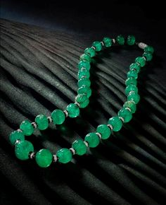 An art deco emerald bead, onyx and diamond necklace, Cartier, circa 1925. Designed as thirty-two graduated fluted emerald beads each with onyx and single-cut diamond rondell spacers, completed by an elongated clasp of pavé-set rose-cut diamonds, mounted in platinum.