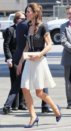 Kate Middleton looked prim and proper in a crochet top with a white pleated knee-length skirt while touring with Prince William. She completed her look with suede Prada pumps. British Airways on July 10, 2011 in Los Angeles, California