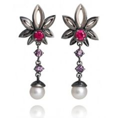 These dramatic earrings are part of the darkly romantic Fiore Della Notte collection by ethical jewellery designer Anna Loucah, originally created for Livia Firth to wear to the 2011 Golden Globes. The Fleur de Lis flowers are created from 18ct recycled white gold, blackened with rhodium plating. The centre of the flower is an ethically mined ruby with drops of purple spinel all sourced from Tanzania by Ruby Fair. The earrings are finished with lustrous CarbonNeutral® Akoya pearls from…