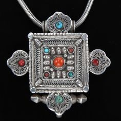 A vintage silver Gau (amulet or prayer box) pendant, decortaed with silver work and coral and turquoise beads, from Tibet. SKU:epe0040  www.tribaljewellery.co