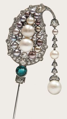 Natural pearl, emerald and diamond jabot pin, Cartier, 1920s. Of Indian inspiration, set with natural pearls of various colours, a circular-cut emerald, cushion-shaped, circular-cut and rose diamonds, suspending a line of diamonds and natural pearls; the keeper set with circular-cut diamonds, calibré-cut emeralds and a natural pearl, signed Cartier, numbered, French assay and maker's marks. #Cartier #vintage #pin