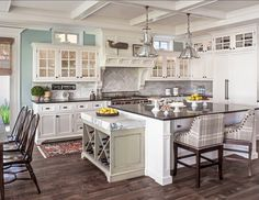 Kitchen Ideas. Great kitchen design ideas. I can't help but fall in love with coastal kitchens whenever I see them. Great reclaimed wood floors against the white cabinets.  Island countertop is honed black granite, except for the wine rack, which is topped with a slab of Carrara marble for rolling out dough. The marble is repeated on the Walker Zanger backsplash tiles, laid in a chevron pattern.  Pendants above island are from Restoration Hardware. #KitchenIdeas #KitchenDesign #WhiteKitchen