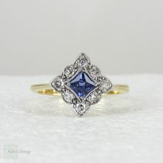 (http://www.addysvintage.co.uk/sapphire-diamond-engagement-ring-art-deco-french-cut-blue-sapphire-with-scalloped-edge-diamond-halo-in-18-carat-gold-platinum/)
