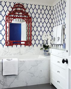 downstairs guest bath? Navy blue and red bathroom features walls clad in navy Moroccan trellis wallpaper lined with a red bamboo pagoda mirror over a marble clad tub accented with white and navy monogram towels.