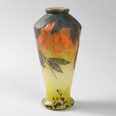 A French Art Nouveau wheel-carved cameo glass vase by Daum, featuring a decoration of orange berries hanging from a tree branch against a mottled orange and yellow ground. A vase with similar decoration is pictured in: Daum, by Clotilde Bacri, Noël Daum and Claude Pétry, Paris: Michel Aveline Éditeur, 1992, p. 95.  Artist: Daum