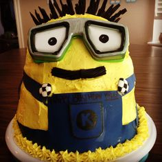 Minion Birthday Cake A six layer cake was trickier than I thought. I had one layer explode an hour before the party. I removed the layer and rebuilt it just in time. I used sugar paper and eatable markers for the cloths. The hair and mouth are cut licorice. The googles are swim googles with photo paper inserted for eyes.  I have a ball cake pan that helped shape the top of the head. My son dreamed up the cake and I had to find a way to build it. Thanks to the Cake Boss I was able to do it…