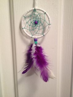 This Car Dreamcatcher has been made on a 2.5 inch brass ring and wrapped with a white crafting yarn. The center has been created using teal