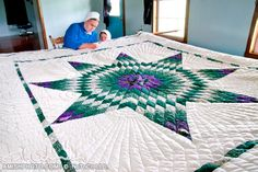 3443 a woman works on an expansive quilt as her daughter looks on -  - amishphoto.com