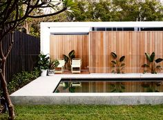 red cedar cladding wraps around the garage and provides a handy nook for poolside chairs. Outdoor Spaces, Outdoor Living, Outdoor Decor, Indoor Outdoor, Pool Plants, Moderne Pools, Cedar Cladding, Art Deco Home, Pool Landscaping