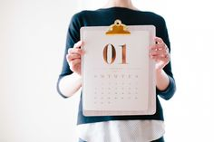 A woman holding up a clipboard with a calendar in front of her chest