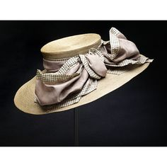 Circa 1910. Made in London. Grey straw hat with a high crown and oval brim trimmed with a wired bow in grey silk taffeta with a black-and-white checked border. Pleated silk under the brim, brown tulle and a black velvet band just inside the crown.