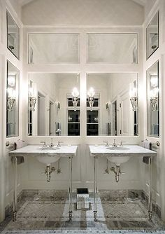 bathroom glam designed by Jamie Herlzinger: mirrored panel walls, marble washstands with lucite legs