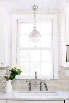 White and gray kitchen features white shaker cabinets paired with white marble countertops and thin gray backsplash tiles.