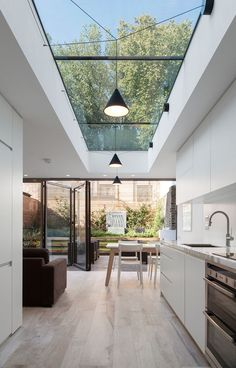 The rear extension to this lower-ground floor flat offers a vista of trees and sky through a long rooflight as well as an adjacent oval version, while full width bi-fold doors create a seamless connection t the beautifully landscaped courtyard garden Modern Kitchen Design, Interior Design Kitchen, Kitchen Designs, Kitchen Contemporary, Interior Garden, Coastal Interior, Minimal Kitchen, Modern Home Interior Design, Beautiful Houses Interior
