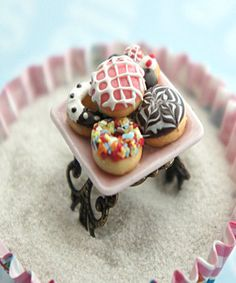 This ring features a miniature plate of handmade donuts sculpted from polymer clay. the ceramic plate measures 1.5 cm x 1.5 cm and is securely attached to an adjustable filigree ring that fits most ri