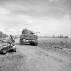 A Sherman tank of the 4/7th Dragoon Guards, 8th Armored Brigade, moves along a road near Rauray, 28 June 1944. Rauray was the HQ of Panzer Regiment 12, 12th SS.
