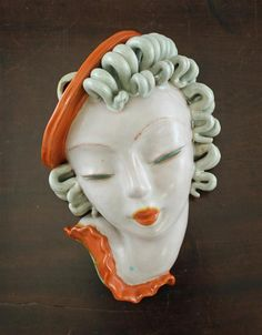 A Goldscheider Art Deco painted terracotta wall mask, of a girl wearing a beret, model no.7523