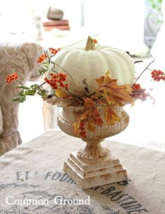 Common Ground: urn planter with leaves and white pumpkin then use for fall decor orlandoweddingflowers/ www.weddingsbycarlyanes.com