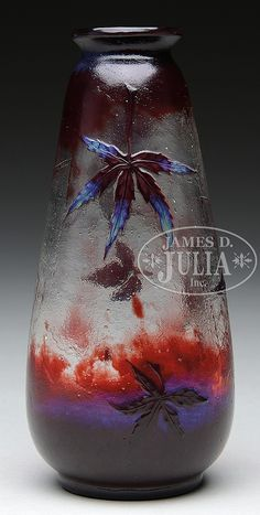"""Galle vase has large delicate cameo spider web on the front with fallen leaves caught in the web. Leaves are done in red cameo with subtle blue opalescence. Back of the vase is decorated with two red cameo leaves falling to the ground, all set against an acid textured clear shading to red background. Signed on the underside with blue opalescence signature """"E. Galle"""" along with a fallen leaf. SIZE: 6-1/2"""" t. PROVENANCE: Dr. Robert LeVere Collection. CONDITION: Very good to excellent. 49726-34"""