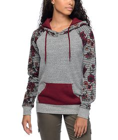 Crafted with a soft nubby fleece construction in a grey colorway, contrasted by a solid burgundy kangaroo pouch pocket and floral details on the sleeves.