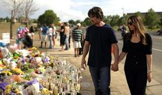 """Christian Bale, who stars in """"The Dark Knight Rises,"""" and his wife, Sibi Blazic, on Tuesday afternoon visit a growing memorial to victims of the Aurora theater massacre, which left 12 dead and 58 wounded. The couple also spent time at Medical Center of Aurora."""