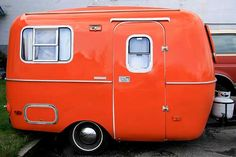 "Isn't she adorable?  Reminds me of a cute couple I met in Moab, Utah.  They had the tiniest orange & navy Boler trailer named ""The Ritz.""  I wonder where Chris & Mokie are now ...    Orange camper"