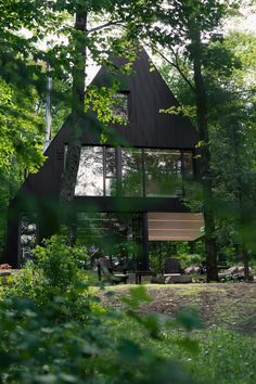Jean Verville architecte designed FAHOUSE, a residence burrowed in the middle of a hemlock forest in Eastern Townships, Canada. The design takes inspiration from the archetypal figure of a house and doubles it with two triangular prism forms that are connected – almost like two trees growing towards the sky.