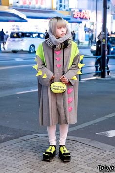 Nosuke's look here features a neon-accented coat from the Japanese brand Zetsukigu with white skinny pants, Ying Yang neon platform sandals from Dog Harajuku, and a mercibeaucoup neon bag.
