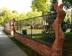 Carved brick columns, wall and steel fence.