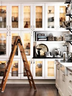 Ikea kitchen with glass front cabinets, open shelves and farmhouse sink