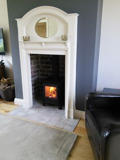 Crisp,  clean,  classic 1930s fireplace with a strongly vertical appearance.   Wish the fire were on the hearth rather than in a stove,  but I love seeing it still used.