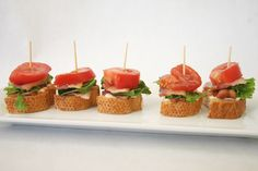 These BLT appetizers are made with mini sized breads also known as canapes, lettuce, tomatoes, bacon and a tooth pick to hold the sandwich together. It's simple fast and ready to be served.