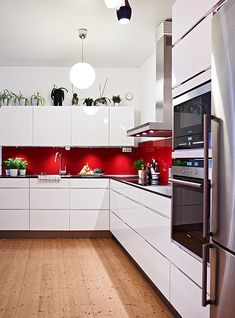 Red Splashback White Cabinets Silver Liances And Wooden Floor