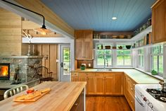 The design of the kitchen in this seasonal retreat was inspired by the homeowner's childhood memories of summers spent on the Maine coast. Bringing this narrative forward, the project combines contemporary efficiency with the feeling of a rustic summer cottage. Marvin windows and doors were smoothly integrated into the precise details of the exterior envelope, enhancing the warm, wood quality of a classic American cottage.   - HouseBeautiful.com