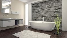 A modern bathroom with free standing bath and slate feature wall