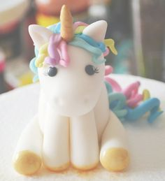 Fondant Unicorn handmade by me. No molds were used to create this beauty. Pretty girly curls make up her mane and tail. Her golden horn and hooves add a little sparkle to this lovely girl. Any unicorn loving child (or adult!) would be happy to have her! Pair this topper with our rainbow and cloud topper for the ultimate unicorn themed party! Shes roughly 3-4in tall from base to the tip of her horn. All toppers will be slightly different in height and appearance since they are all handmade…